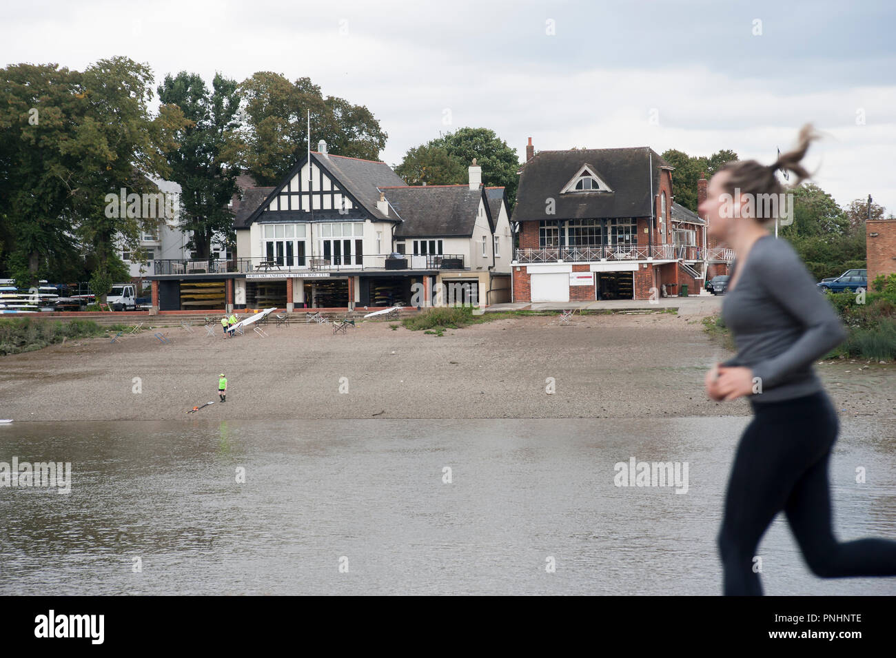 Female jogger running past Mortlake and Anglian Boat Club, London, UK. on opposite bank of River Thames. - Stock Image