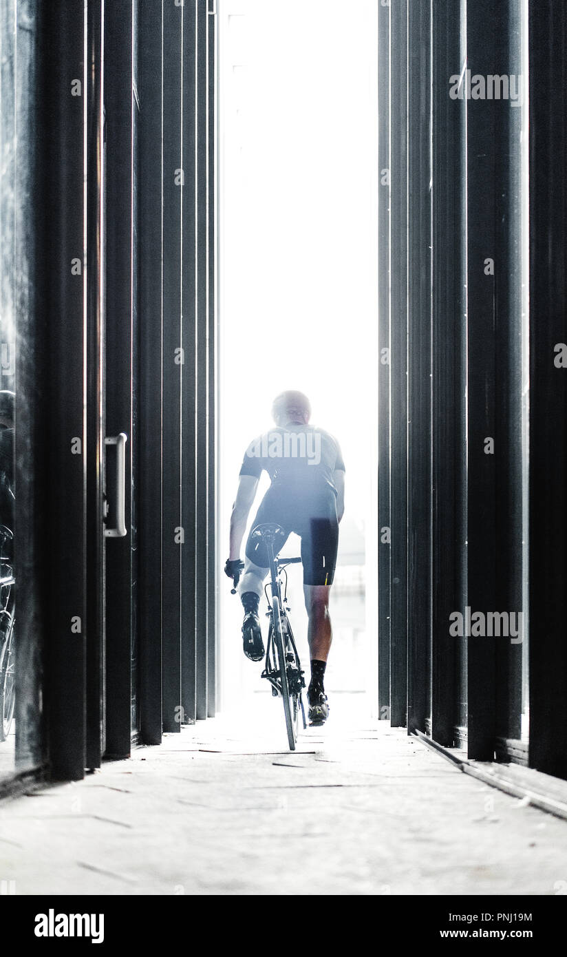Sport bike man riding inside urban glass tunnel with light. - Stock Image