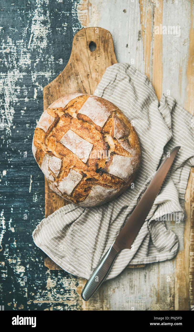 Flat-lay of sourdough wheat bread over linen napkin - Stock Image