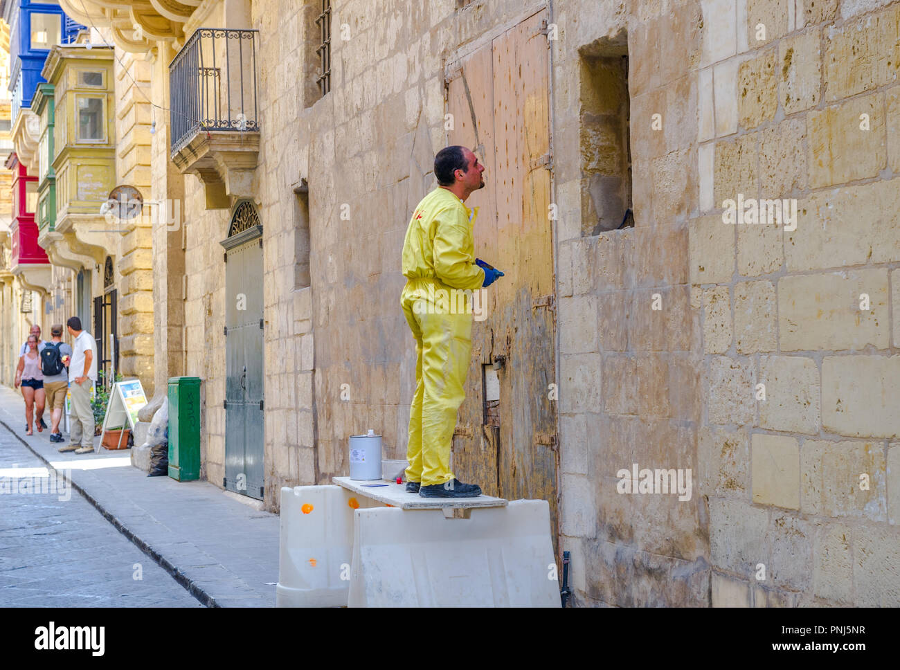 Workman using paint stripper wearing overalls but no eye protection. - Stock Image