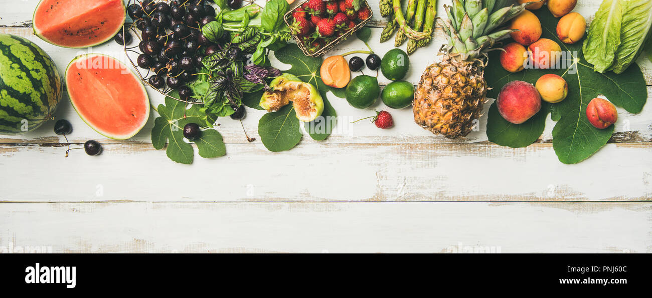 Seasonal fruit, vegetables and greens over wooden background, wide composition - Stock Image