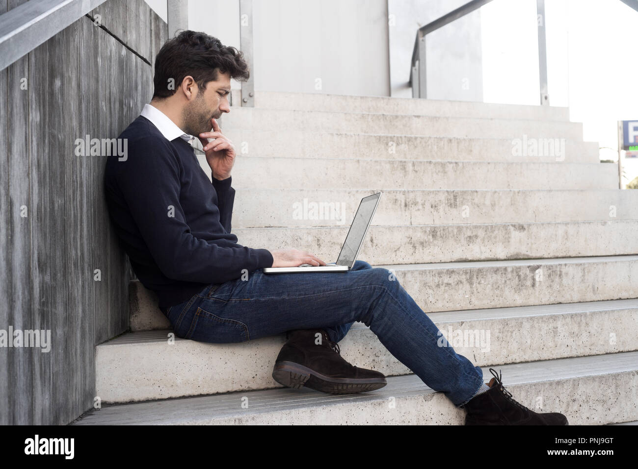 young man with computer and doubts - Stock Image