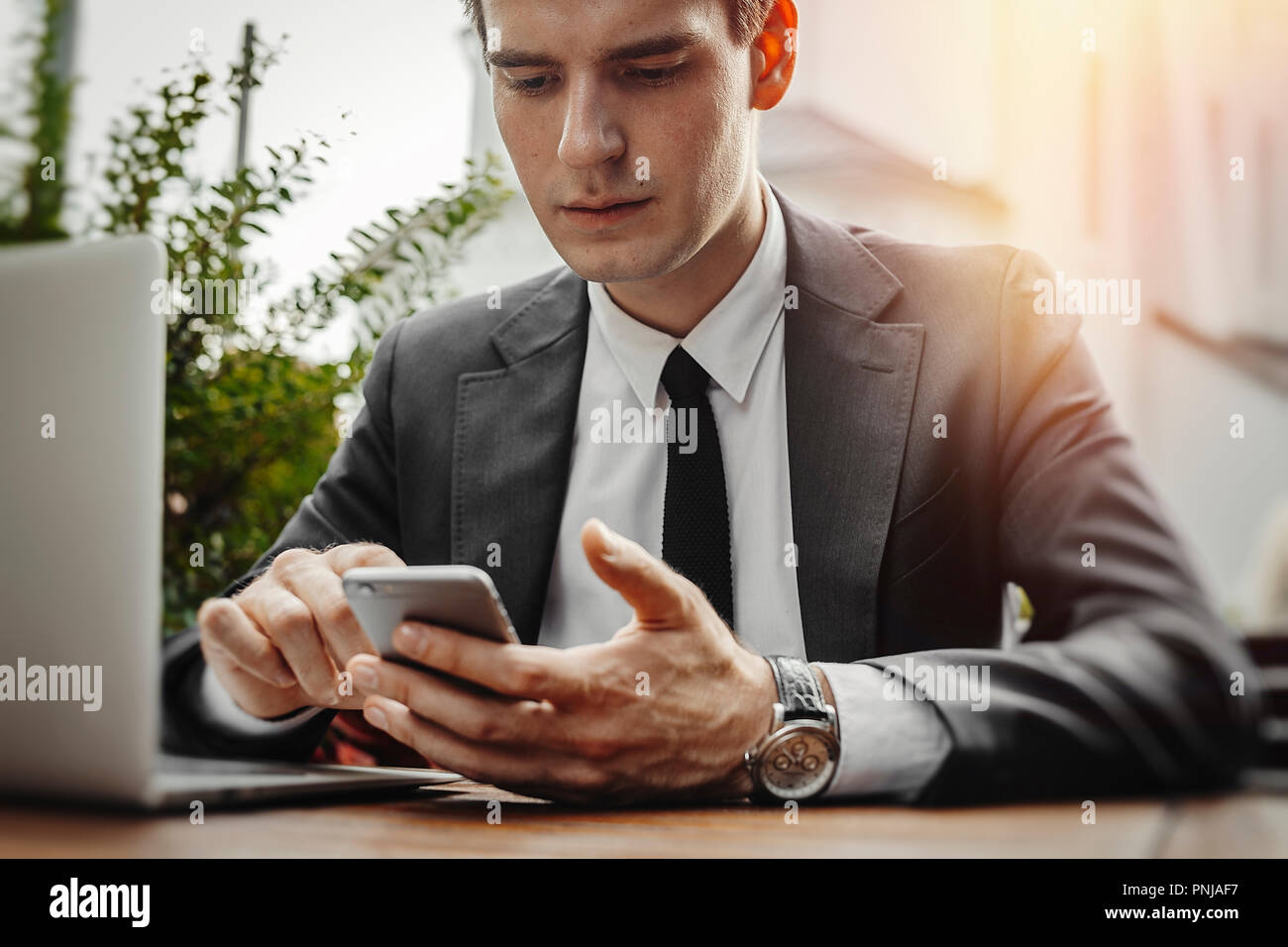 Close up of businessman looking at screen of mobile phone at street cafe. - Stock Image