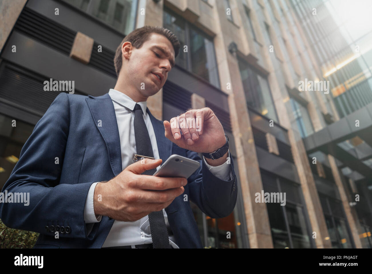 Close up of businessman holding mobile phone in hand and looking at watches. - Stock Image
