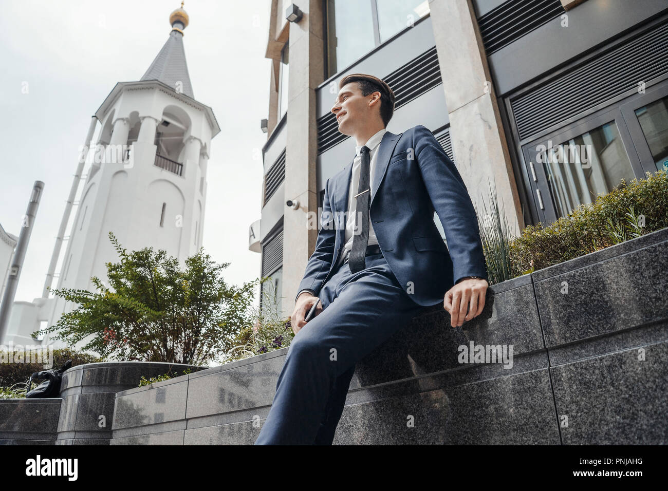Businessman next to business center at downtown waiting for a meeting. - Stock Image