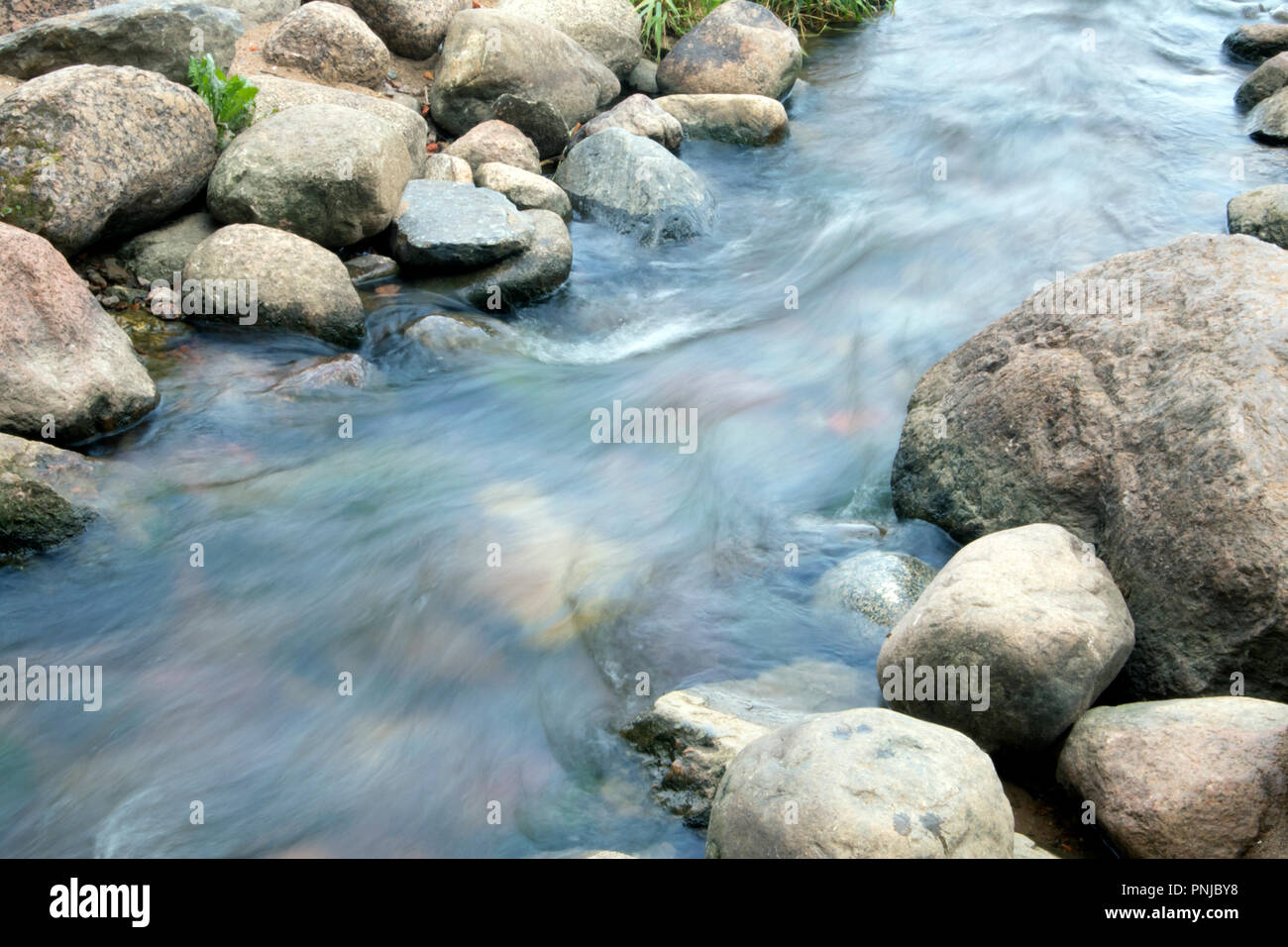 Small creek with stony bottom, rapid stream running between boulders, smoothed water surface Stock Photo
