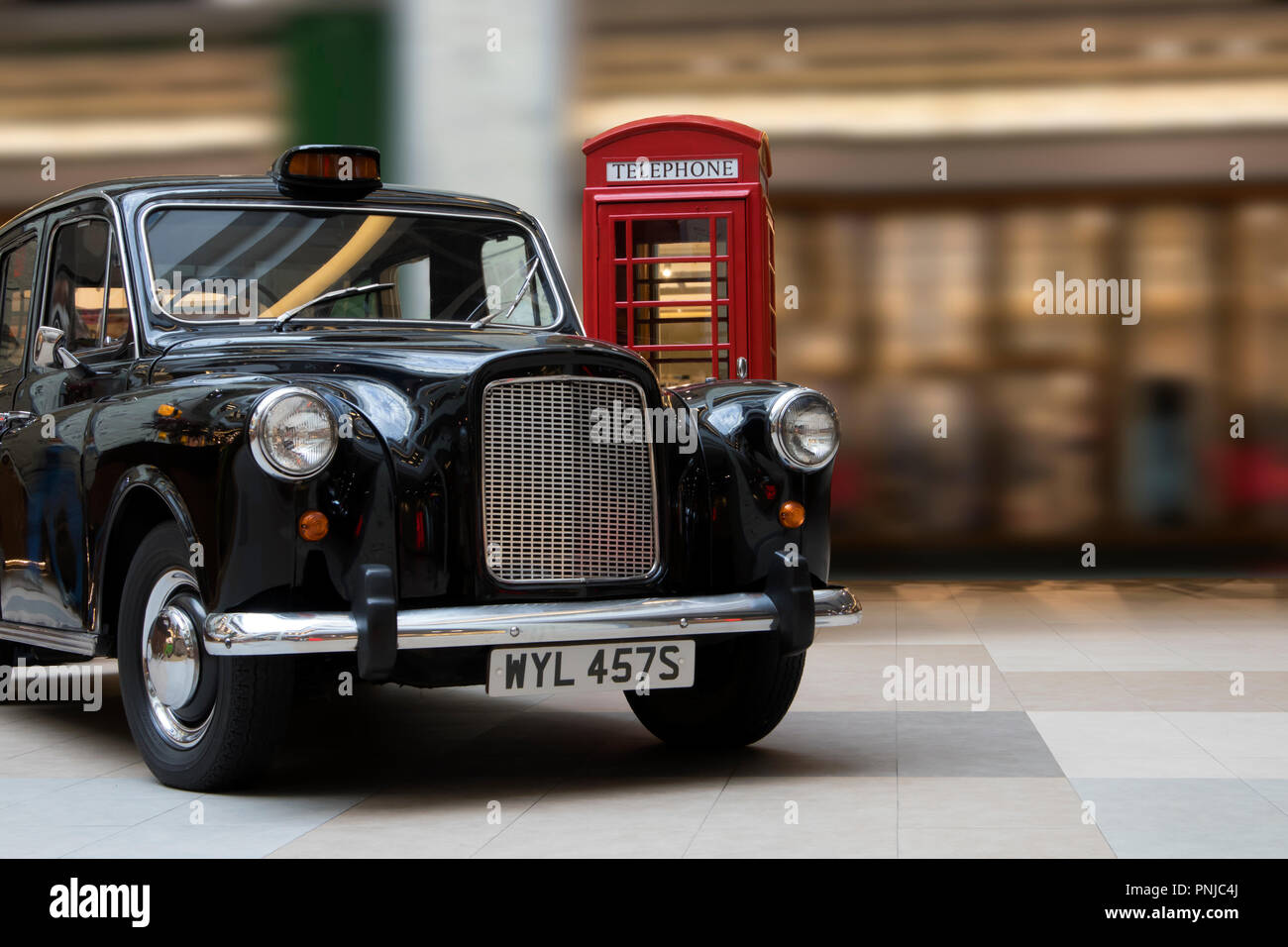 Luxurious old retro automobile and vintage red call box exhibited in a large hall of big moll - Stock Image