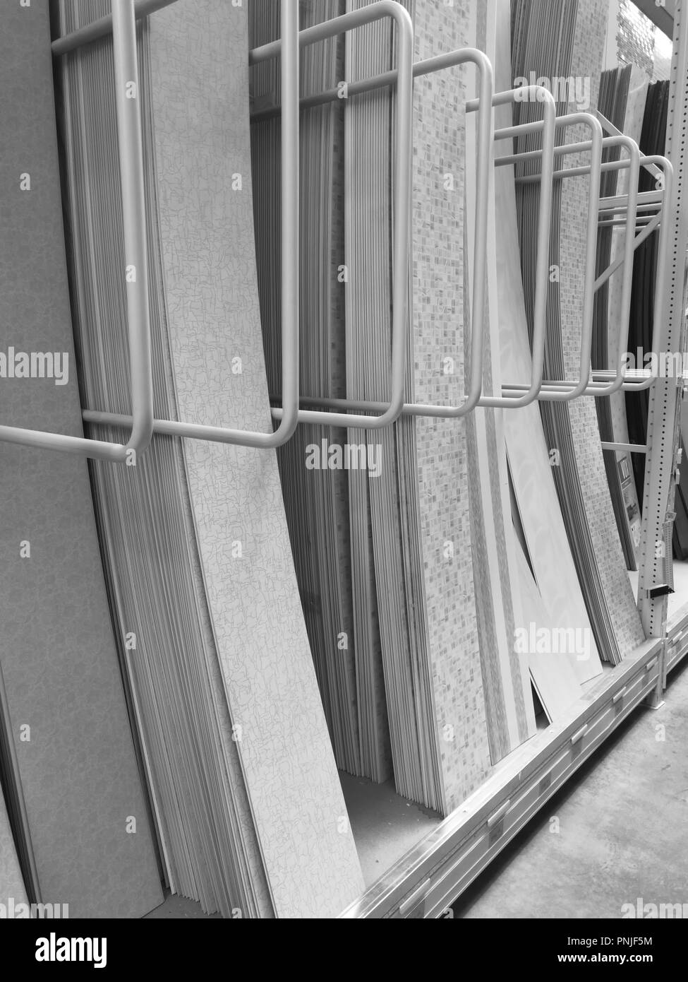 Black and white photo. Sale of PVC panels in the hardware store. - Stock Image