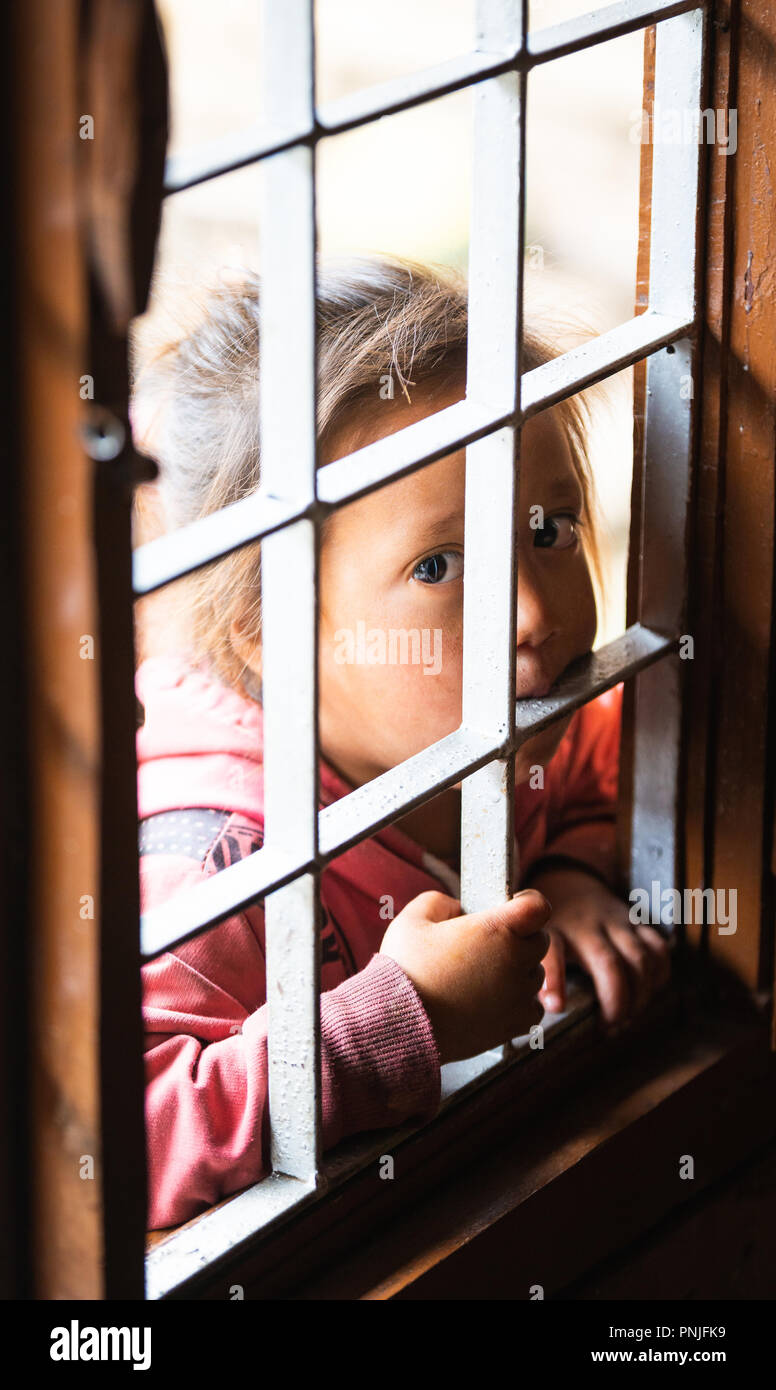 GHALEGAUN, NEPAL - CIRCA MAY 2018: Young Nepali girl looking through an open window with grill. - Stock Image