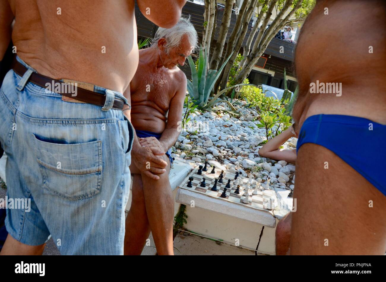 older men playing outdoor chess by the seaside in budva montenegro - Stock Image