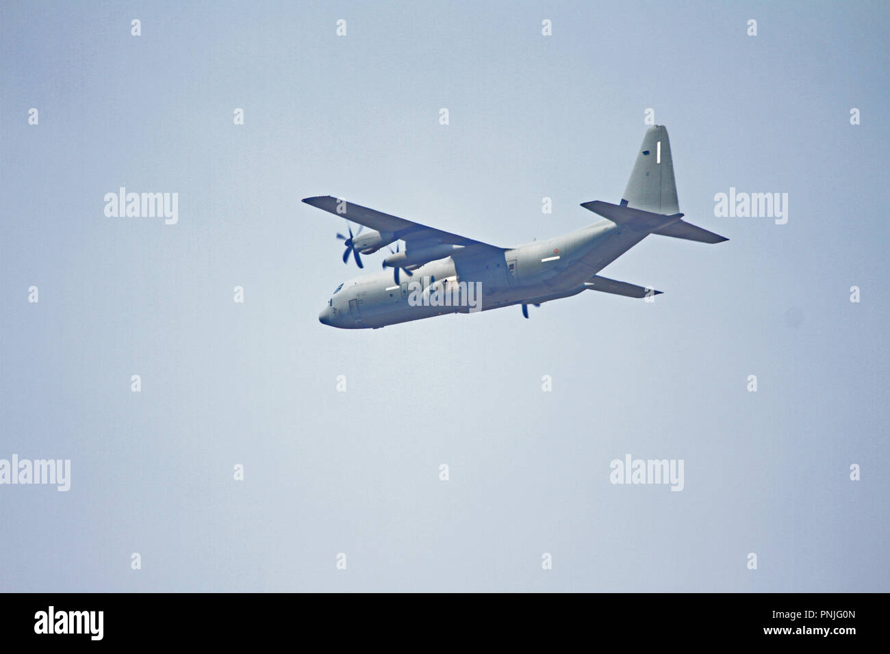 Italian military transport plane or aircraft flying low in the sky in summer in Italy with identifying marks covered over Stock Photo