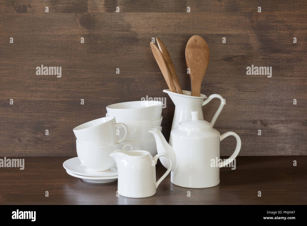 Crockery, porcelain, white utensils and other different stuff on wooden countertop. Kitchen still life as background for design. Copy space. Stock Photo