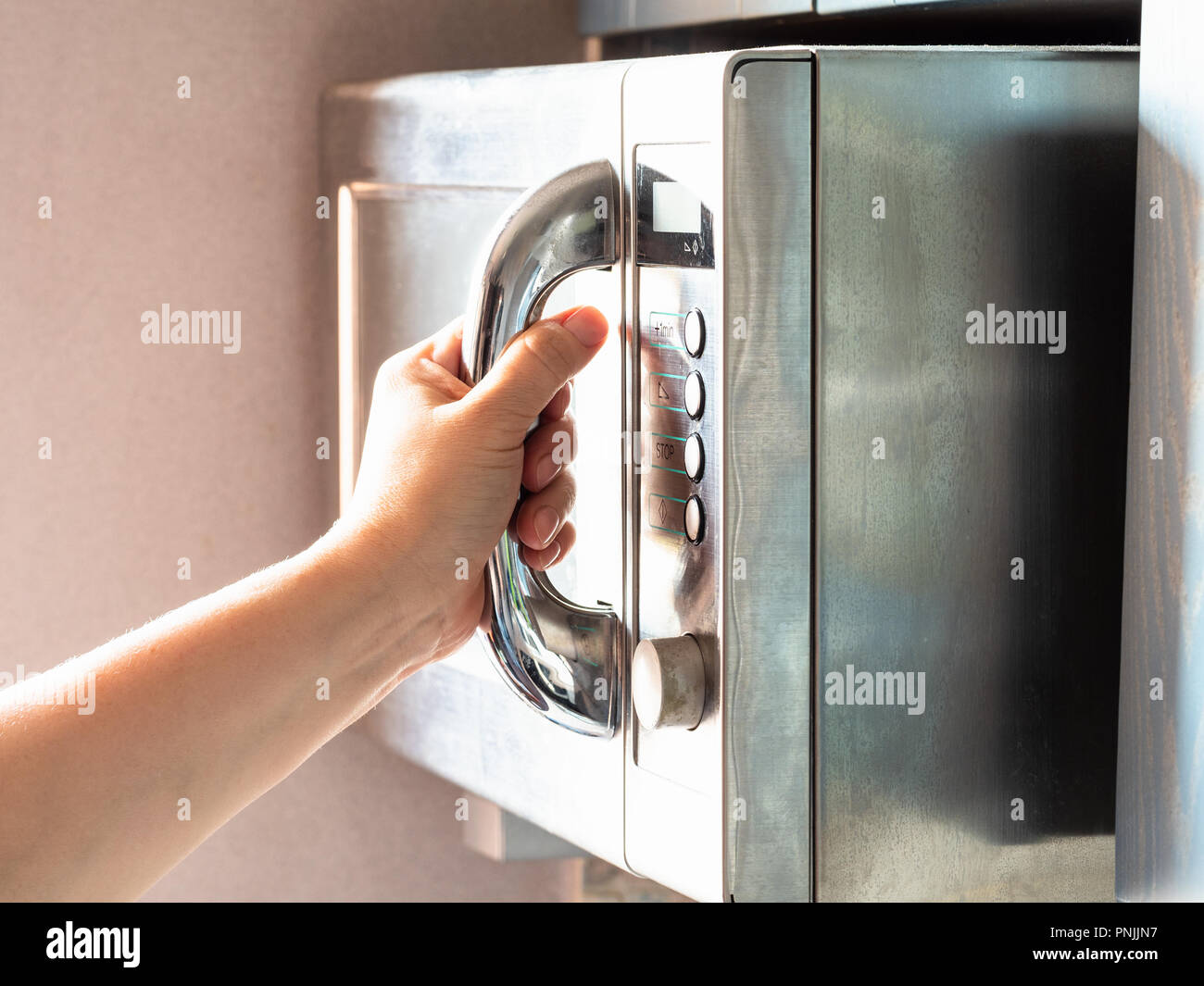 the illuminated by sun hand closes door of old steel microwave oven at home - Stock Image