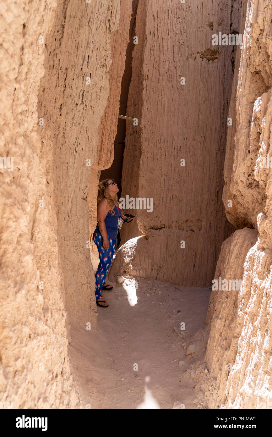 Blonde female hiker stares up the canyon walls inside of Cathedral Gorge State Park in Lincoln County Nevada USA - Stock Image