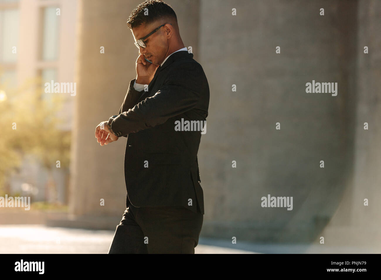 Man in formal clothes looking at his wrist watch and talking over mobile phone while walking on street. Busy office going person walking on street loo - Stock Image
