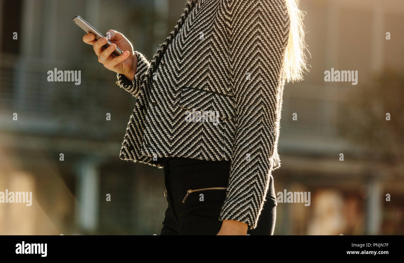 Mid section of a woman using her mobile phone while commuting to office. Busy office going woman walking on street and using her mobile phone with sun Stock Photo