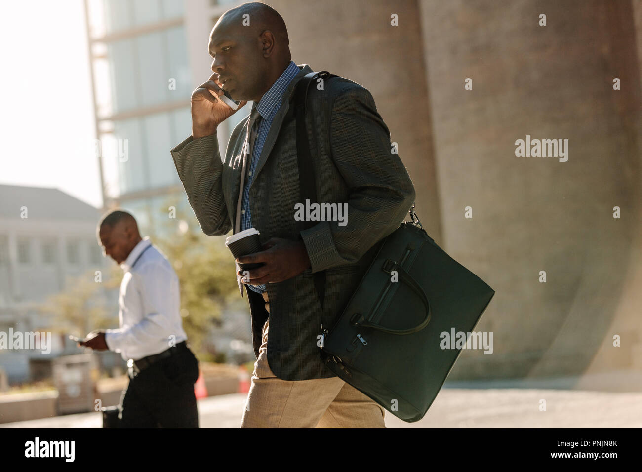 Men using mobile phone while commuting to office. Businessmen leading a busy life using mobile phones and drinking coffee while walking on street to o - Stock Image