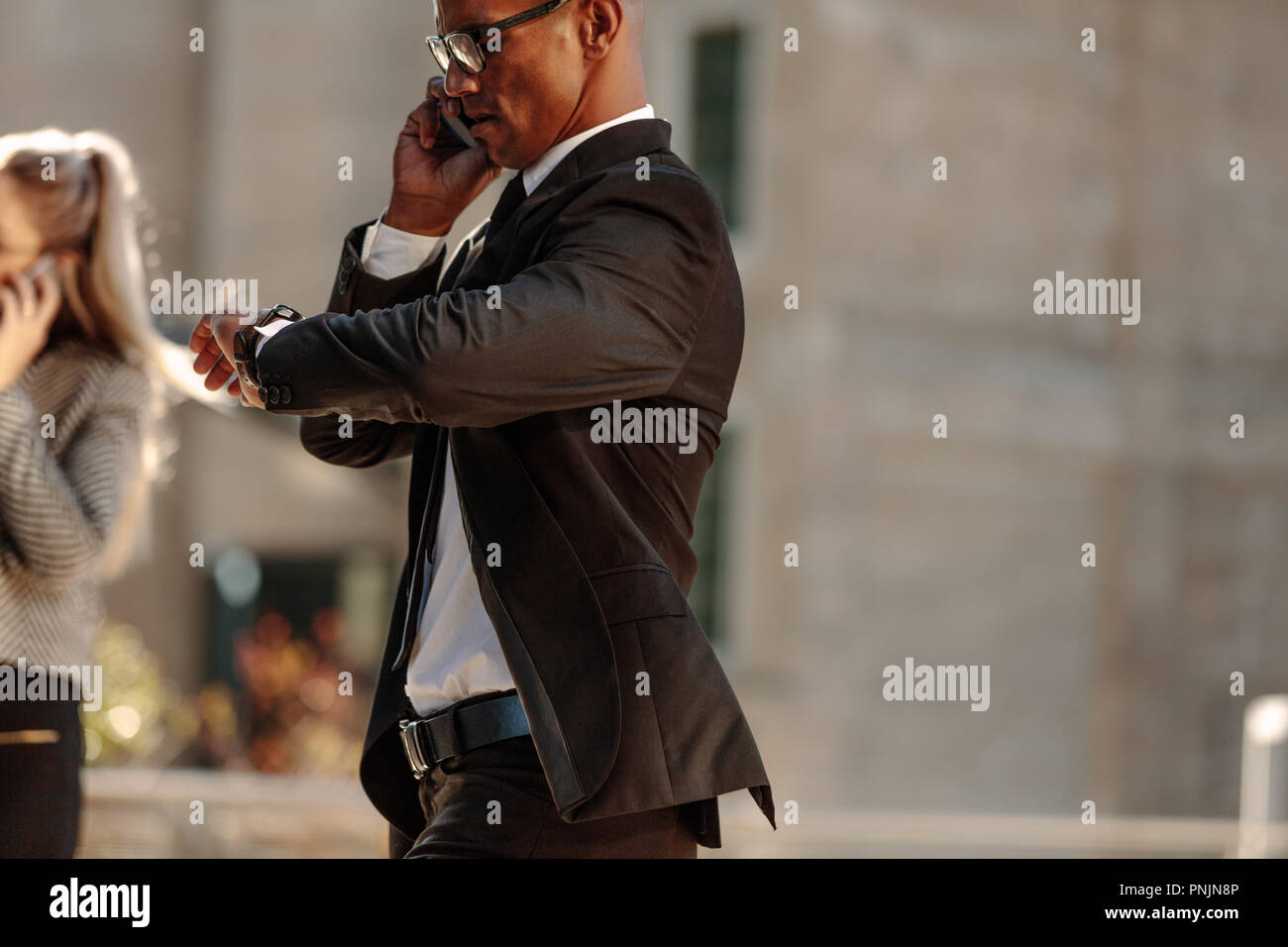 Man looking at his wrist watch and talking over mobile phone while commuting to office in the morning. Businessman checking time while walking to offi - Stock Image