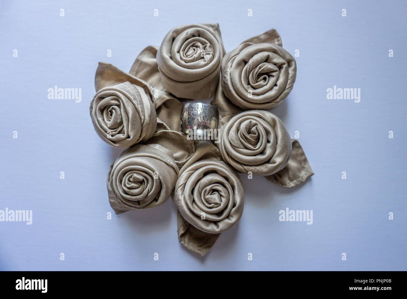 Golden Napkin Origami Roses In A Circle With Silver Metal Ring In