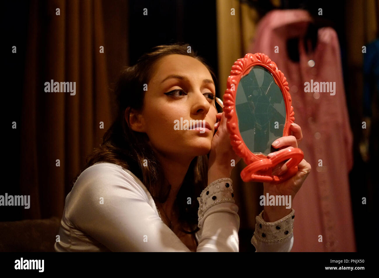 A Young Dancer Looking In The Mirror And Applying Makeup On Eyebrow