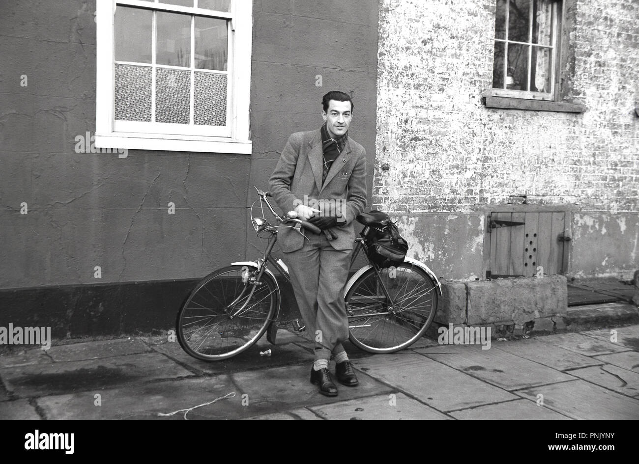 1950s, historical, cycling to work...adult male cyclist in clothing of the era and with bicycle clips, posing for a photo in a street in the city of Bristol, England, UK. Traditional 'city' or urban bicycles such as these were an important means of transport in post-war Britain. - Stock Image