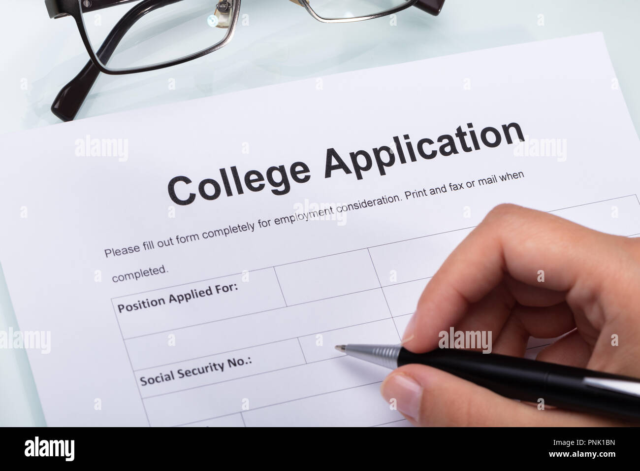 Close-up Of A Person's Hand Filling College Application Form With Pen Stock Photo