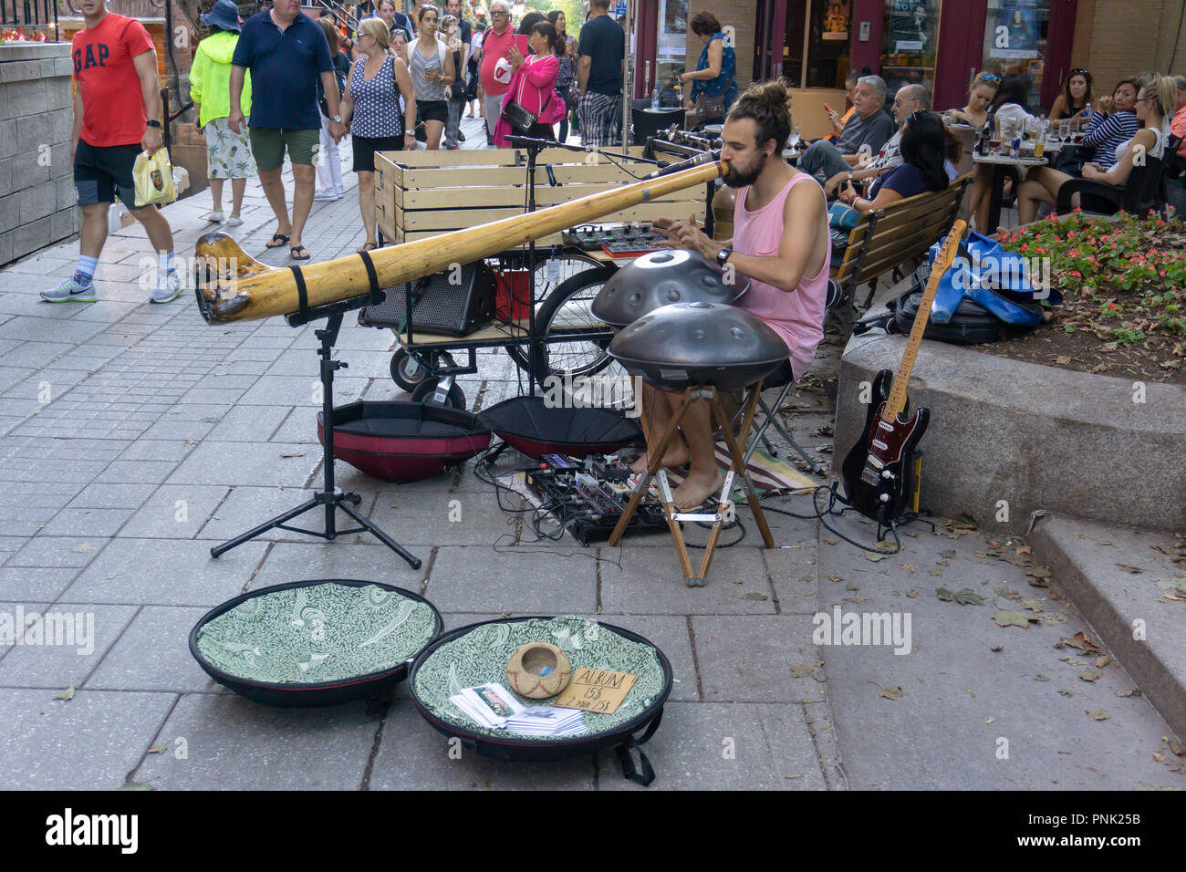 Musician playing on long wooden horn instrument in old Quebec City - Stock Image