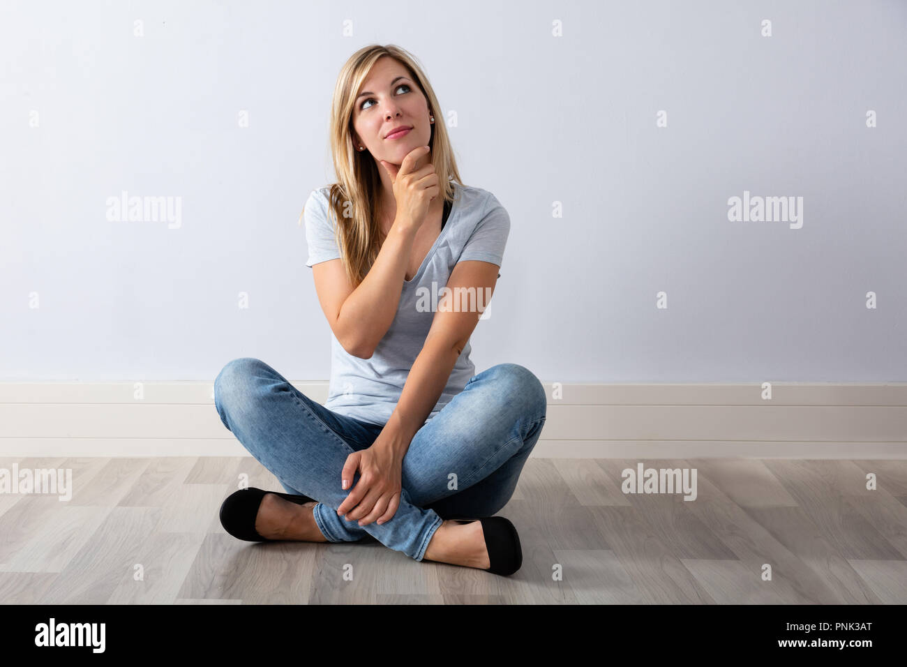 Portrait Of A Contemplated Young Woman Sitting On Hardwood Floor - Stock Image