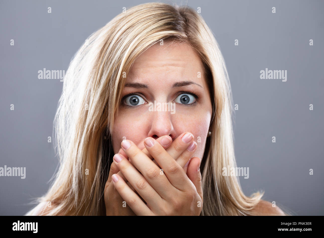 Shocked Woman With Hand On Mouth Over Grey Background - Stock Image