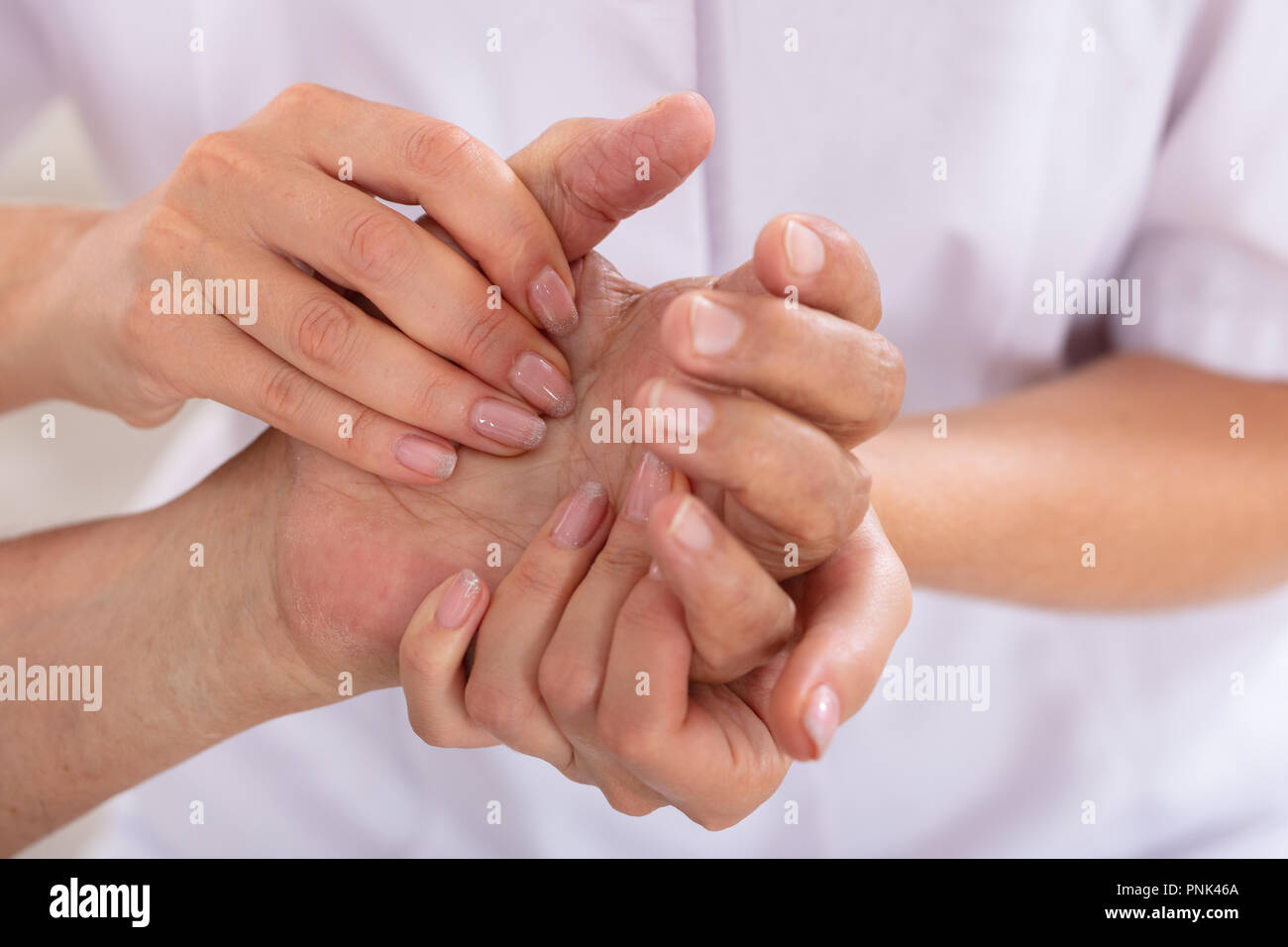 Close-up Of A Female Doctor Examining Patient's Wrist - Stock Photo