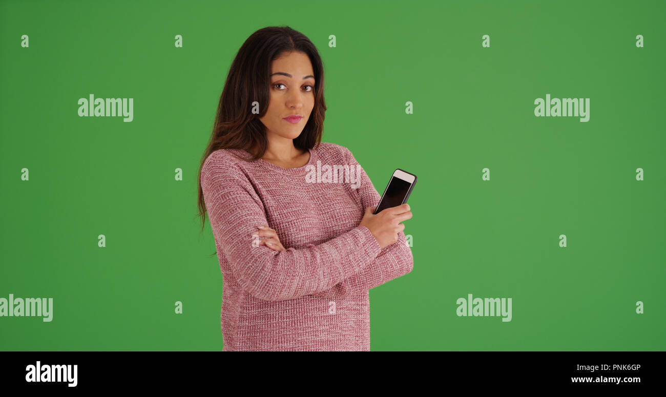 Latina female in pink sweater posing with cellphone on green screen - Stock  Image