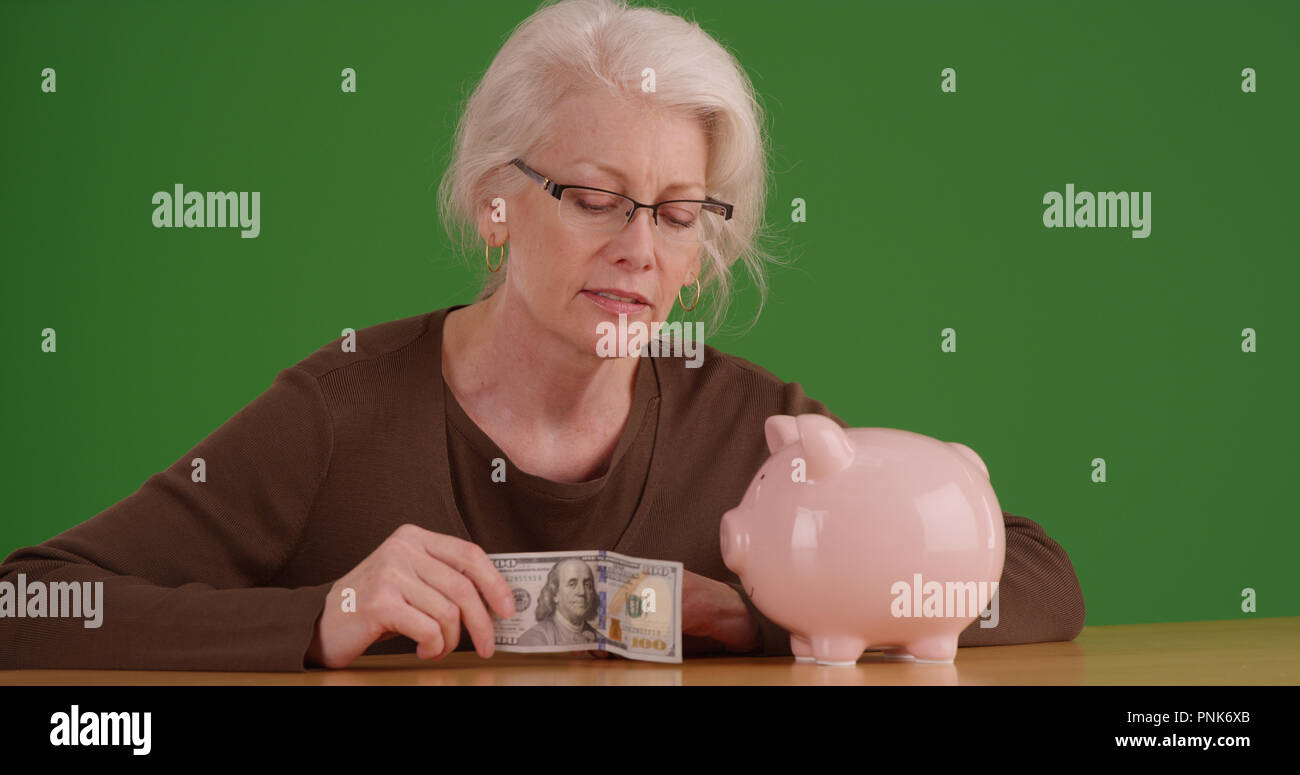 Elderly woman about to put 100 dollar bill into piggy bank on green screen Stock Photo