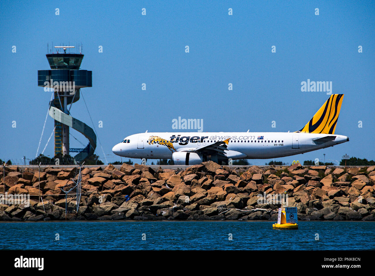 Sydney, New South Wales, Australia - November 7. 2013: Tiger Airways commercial passenger jet aircraft taxing past the control tower. - Stock Image