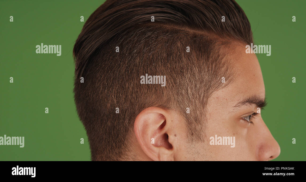Side View Of Young Millennial Man With Undercut Standing On Green Screen Stock Photo Alamy