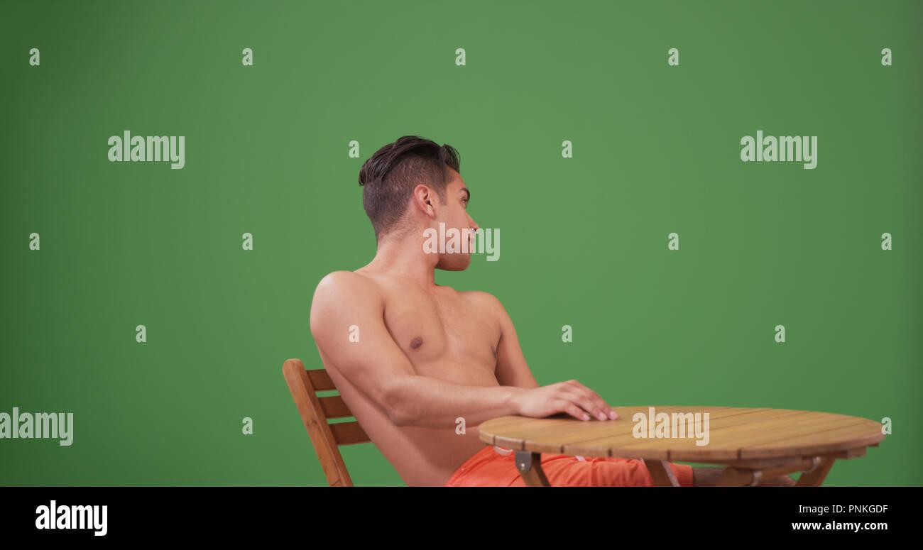 Millennial Hispanic man wearing swim trunks sitting on green screen - Stock Image