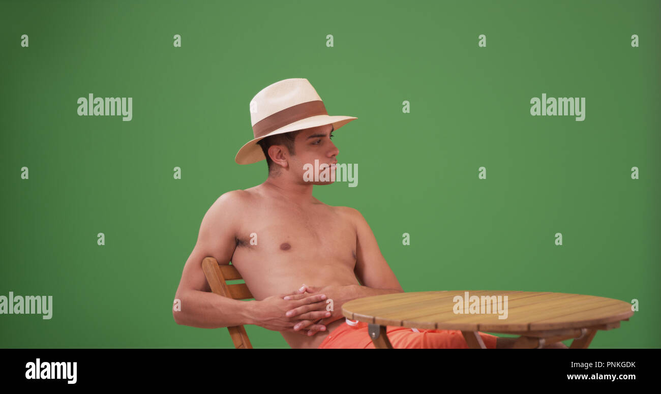 Millennial Latino man in swim trunks and fedora sitting on green screen - Stock Image