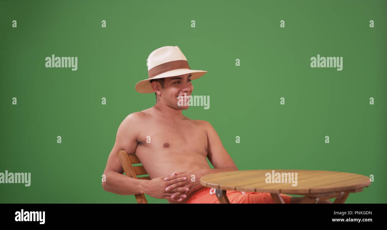 Millennial Latino man in swim trunks and fedora enjoying himself on green screen - Stock Image