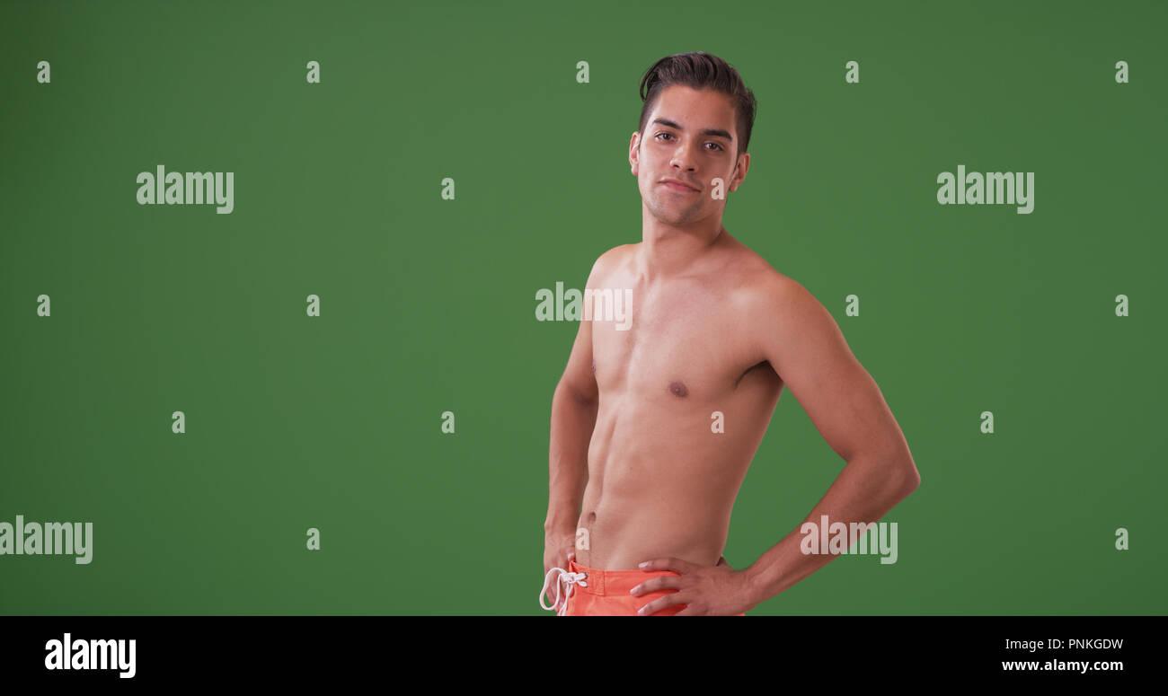 Handsome Hispanic man in swim trunks posing on green screen - Stock Image