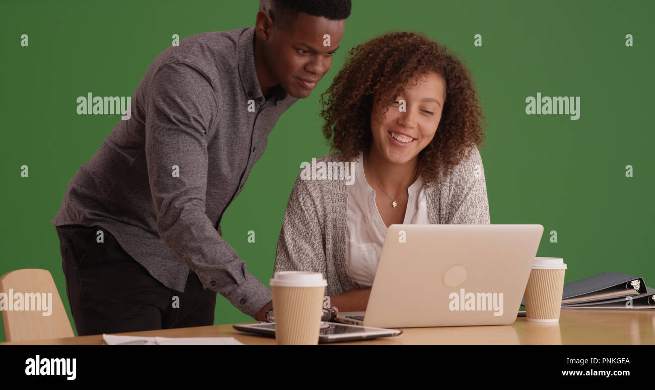 Young happy office co-workers using a computer on green screen - Stock Image