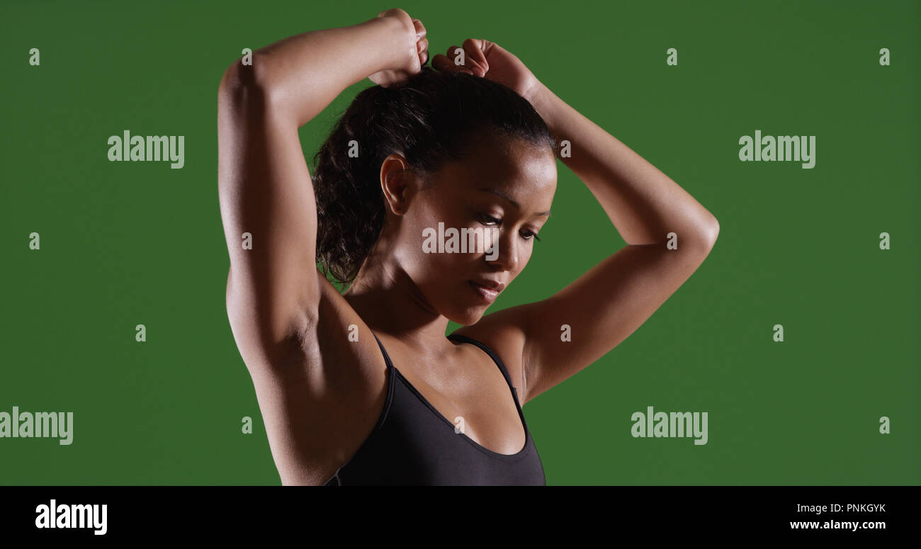 Strong Asian woman tying hair back before workout on green screen - Stock Image