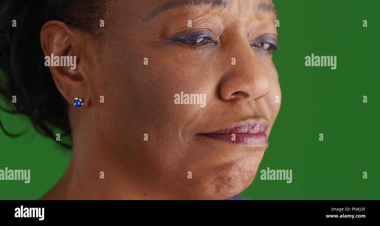 Closeup of teary-eyed black senior woman on green screen - Stock Image