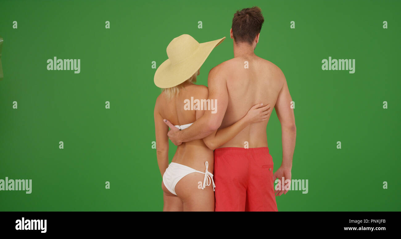 Rear view of white couple in swimwear holding each other on green screen - Stock Image