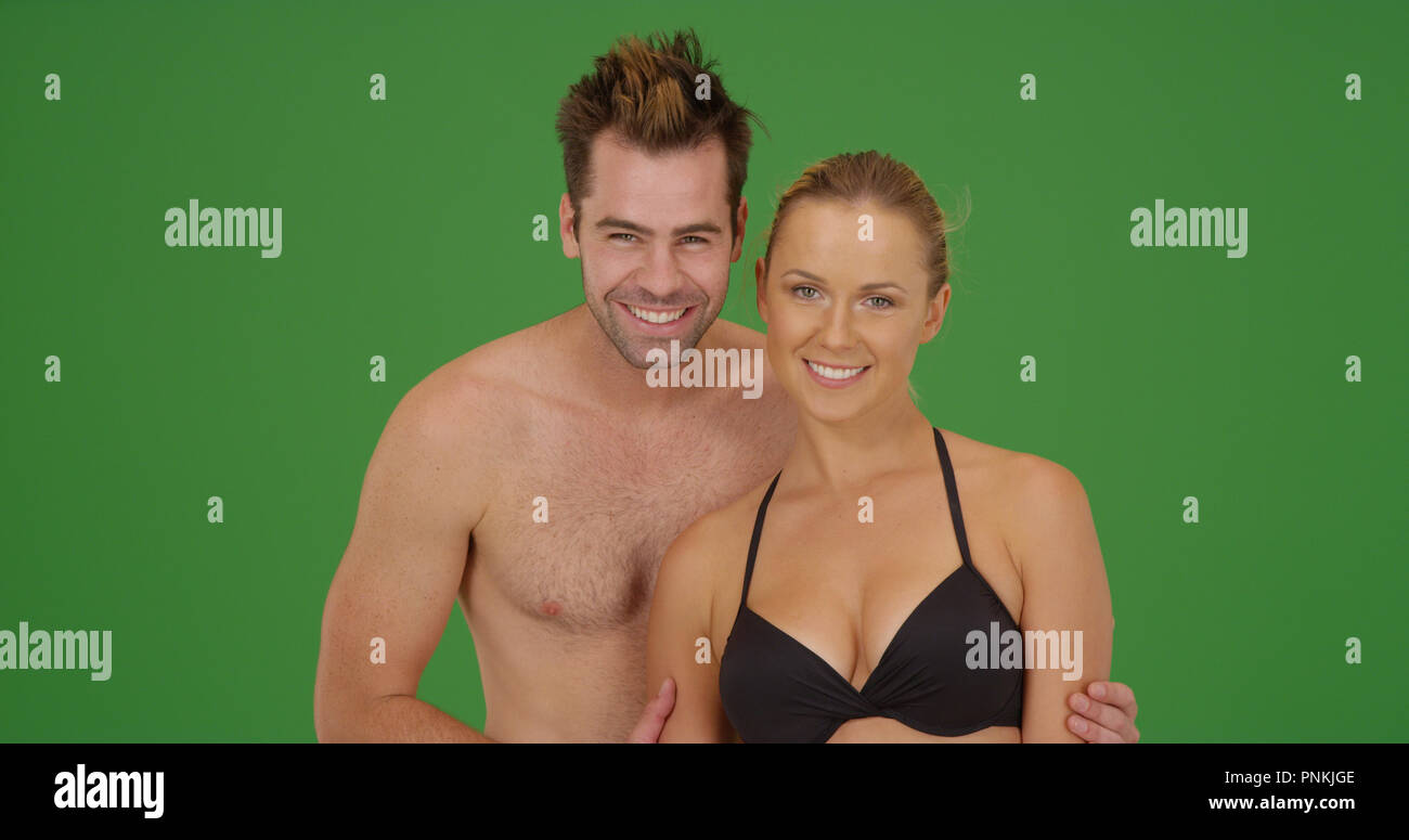 dd9839e4a3 Caucasian millennial couple in swimsuits smiling at camera on green screen  - Stock Image