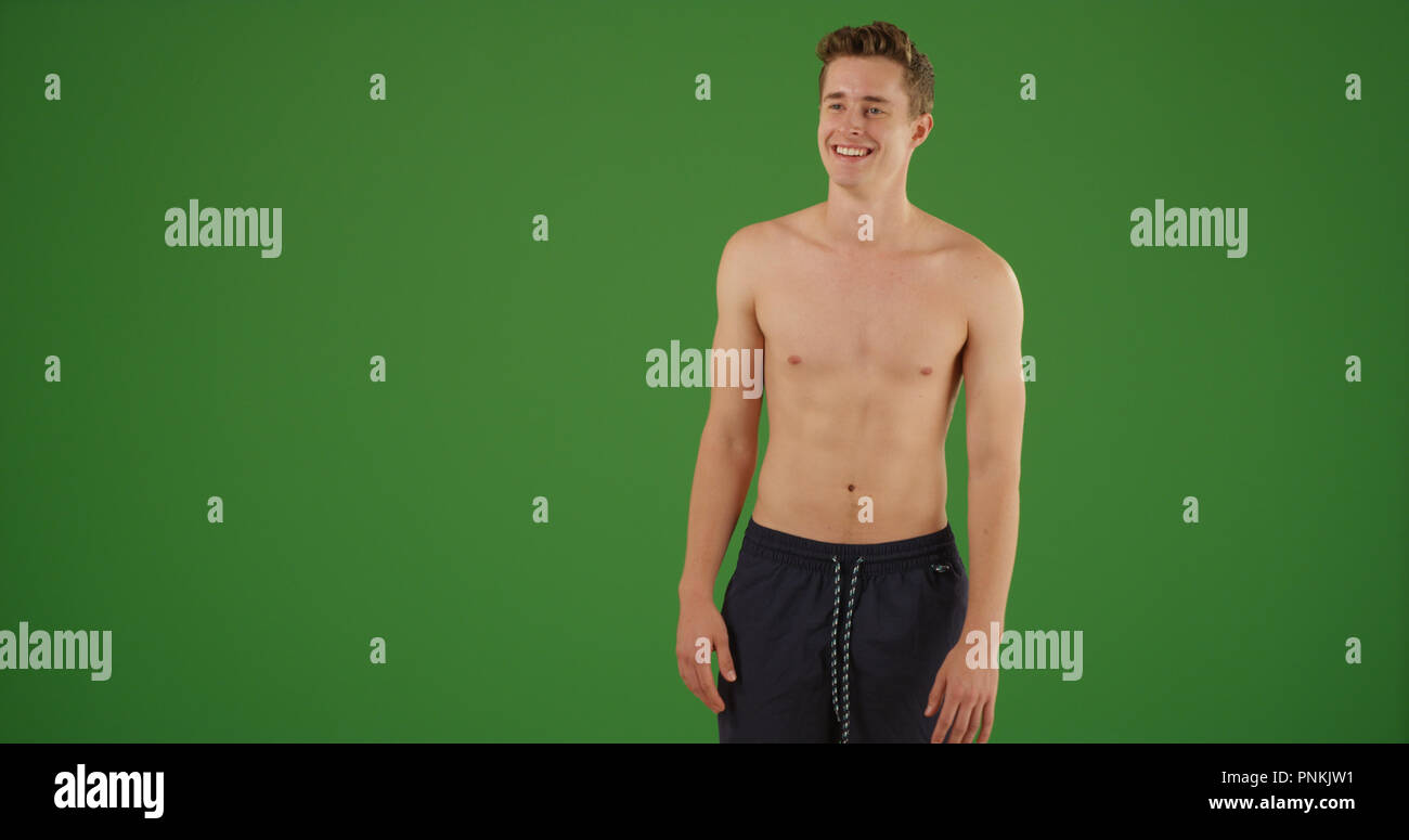 41d67a20d61cc Young fit handsome white guy standing in swim trunks on green screen -  Stock Image