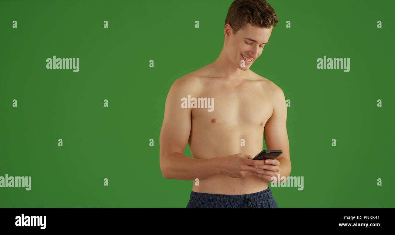ff1f0e8ce0 Happy young man texting with cell phone in his swim trunks on green screen  - Stock