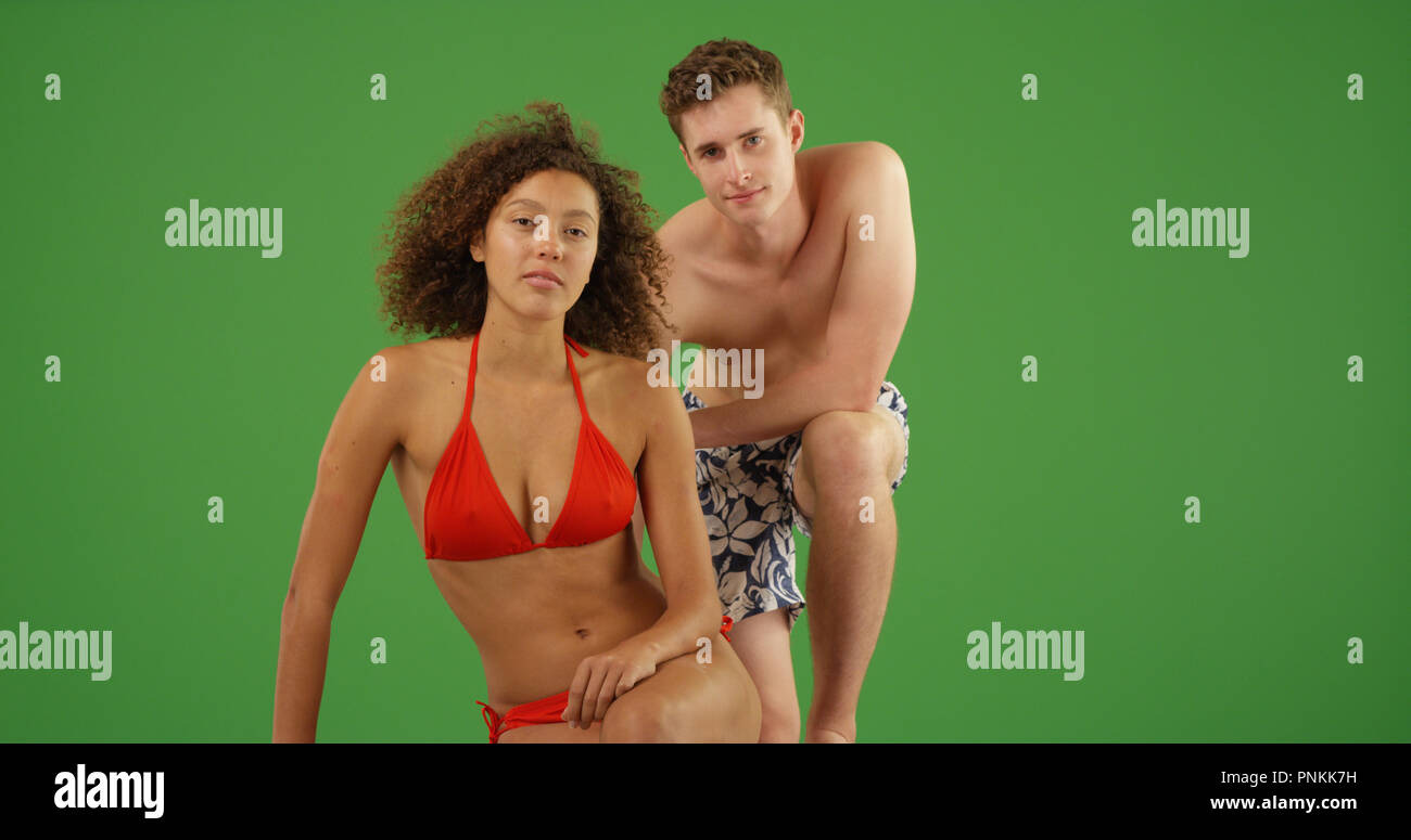 e47fb7c2092e6 Black bikini girl posing with white male in swim trunks on green screen
