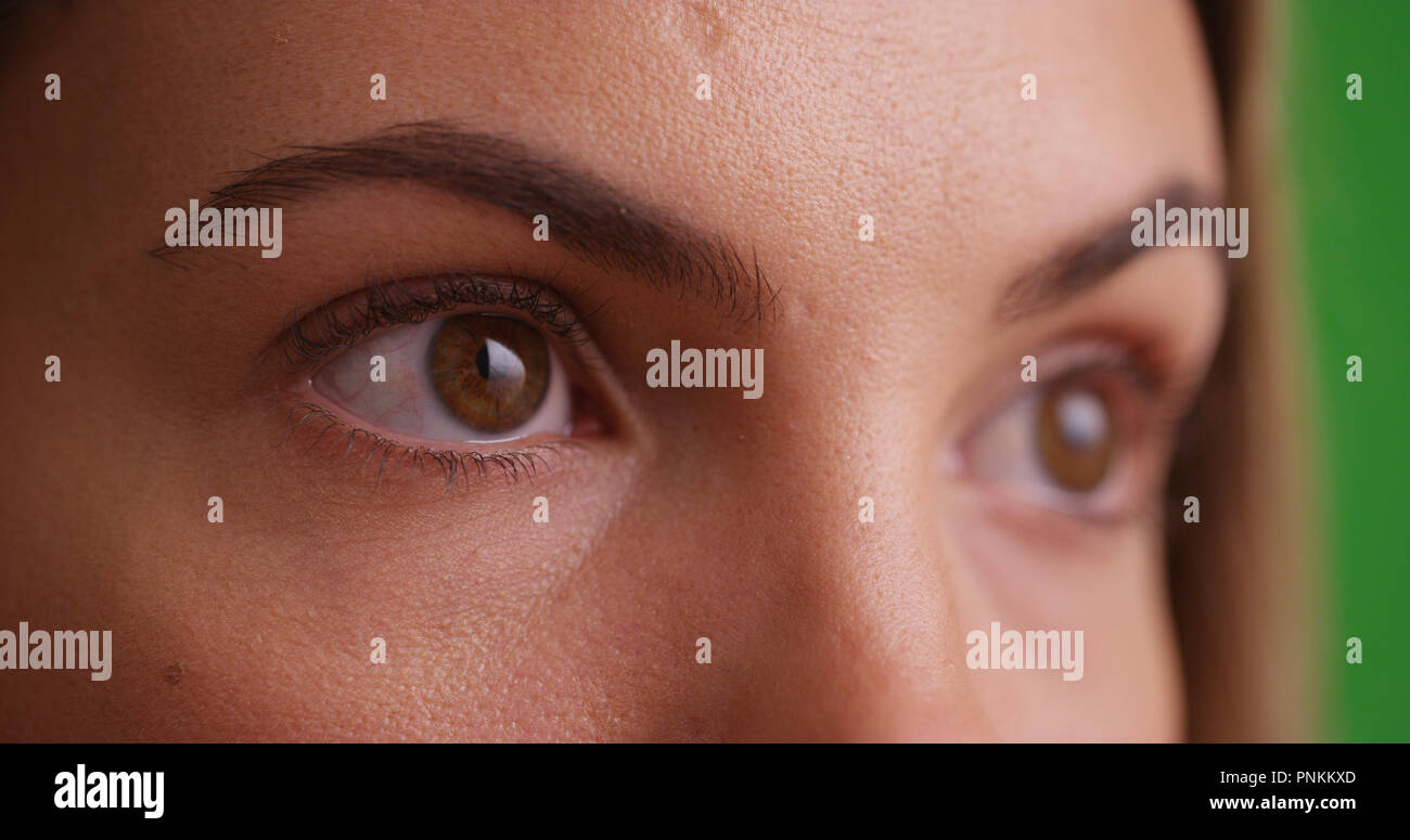 Close view of millennial brunette's eyes looking offscreen on green screen - Stock Image