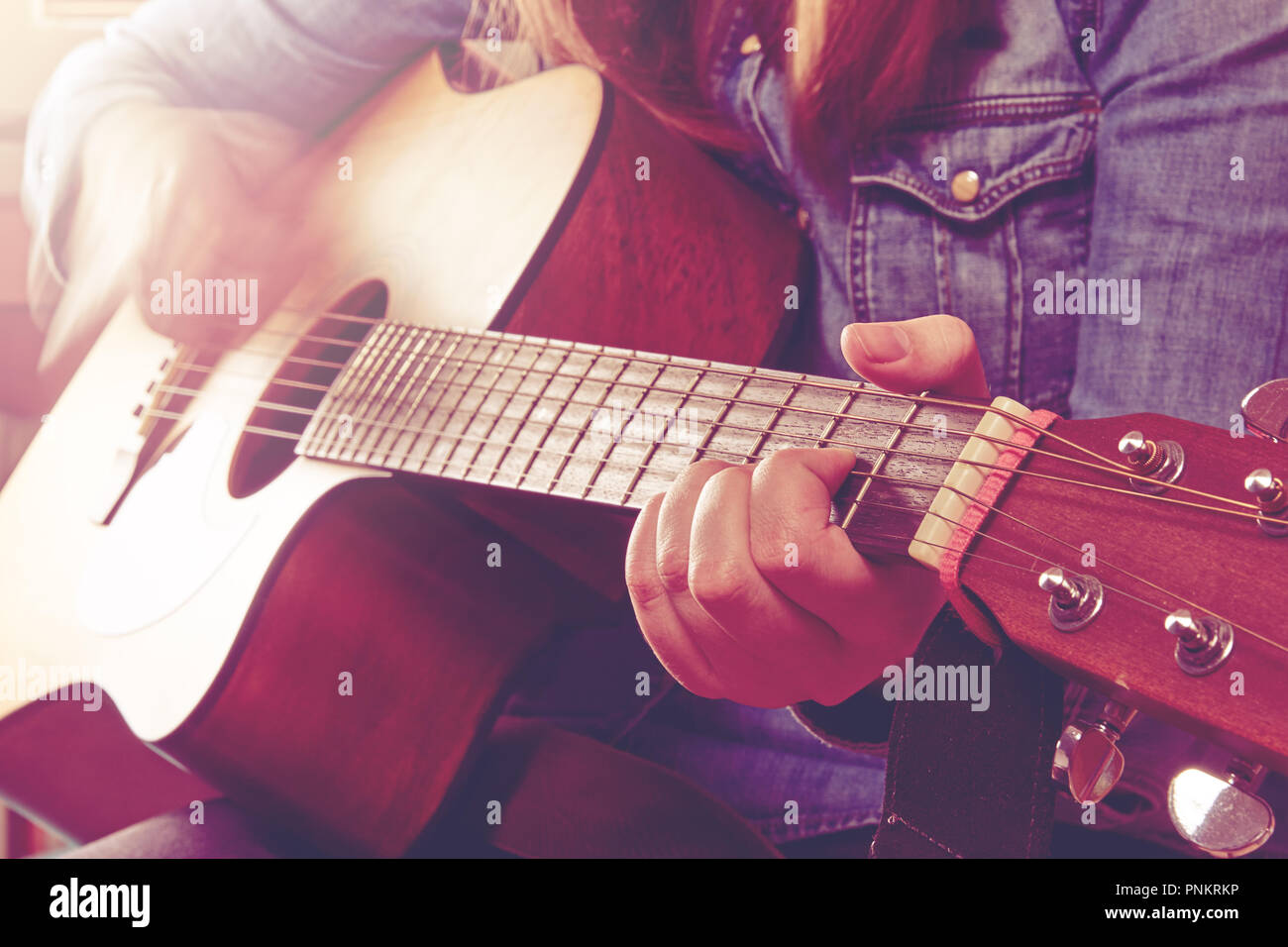 Young Woman Playing Guitar And Holding Fingers Chord Close Up Photo