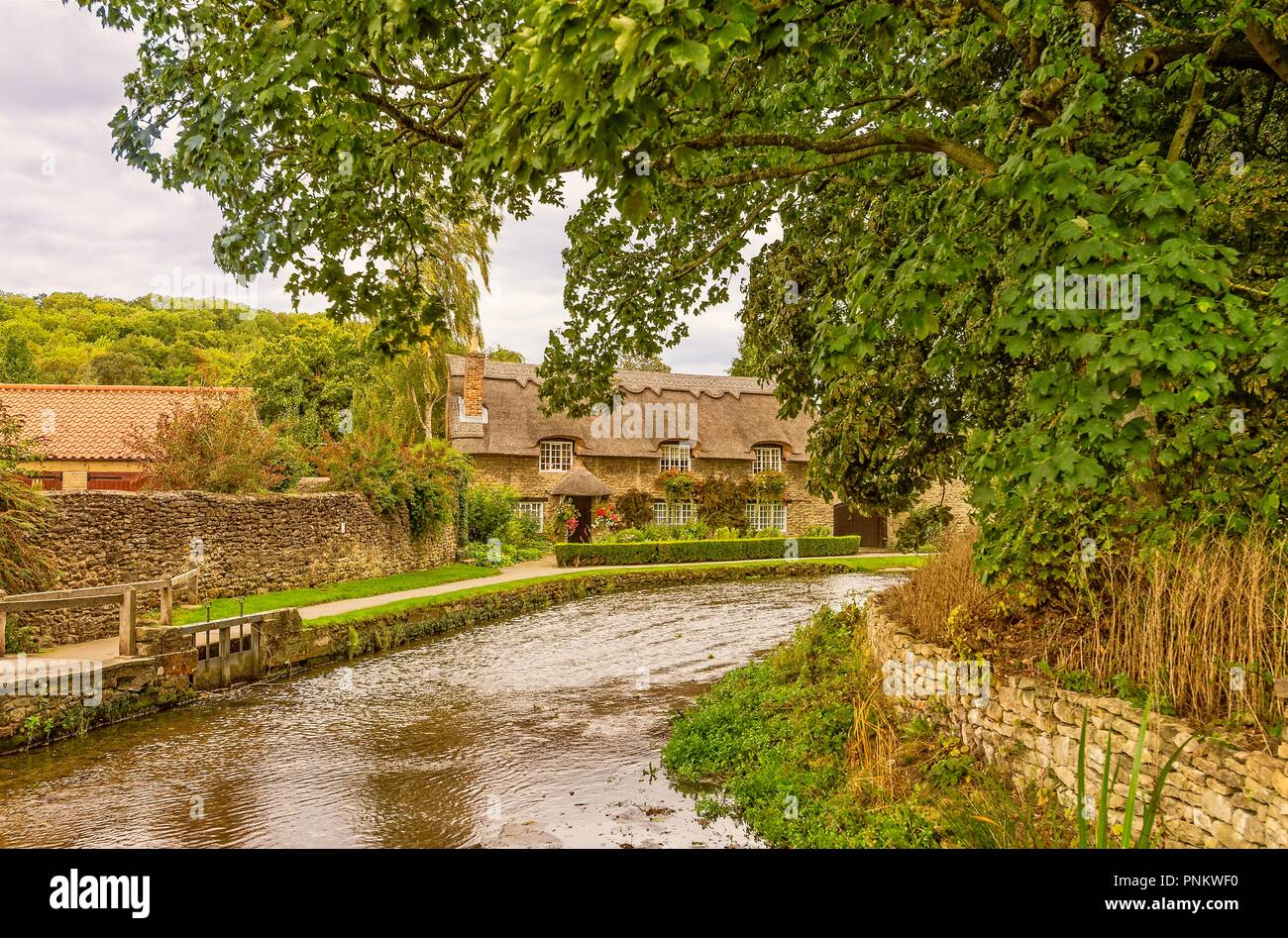 Stone-built picturesque thatched cottage in Thornton-le-Dale, North Yorkshire.  A path follows the curve of the river as it flows passed the house. Stock Photo
