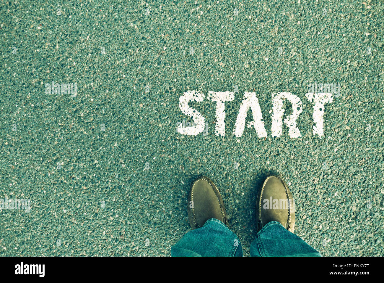 feet and legs of a man standing near the word START, conceptual image for a new beginning or competition in business - Stock Image